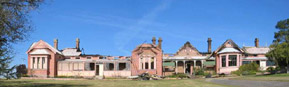 Photo by Ross Thompson of the Old Bega Hospital after the 2004 fire, missing most of its roof and no glass in the windows